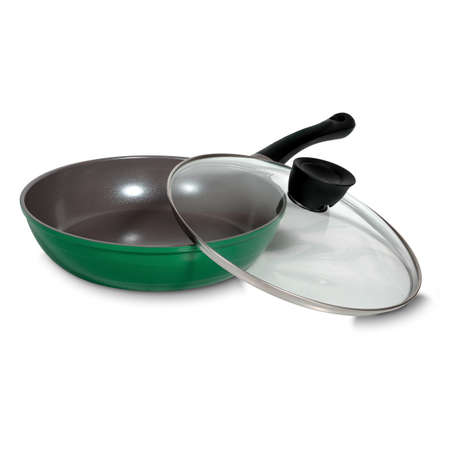 A green round frying pan with a transparent lid lying next to it for cooking, kitchen utensils, dishes. Side view isolated on white Standard-Bild