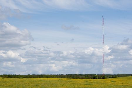 horison: Navigation antenna, sky background, blossom meadow and trees at bottomAnt