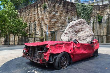 Big and heavy stone crush a red car Editöryel
