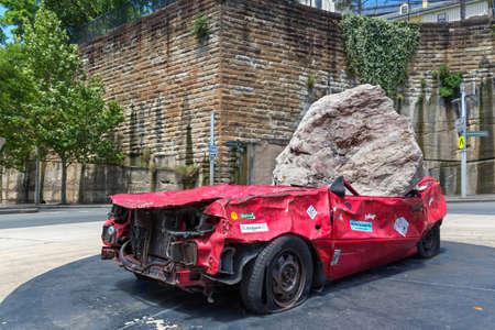 Sydney, Australia - January 9: Big and heavy stone crush a red car on January 9, 2019 in Sydney, Australia.