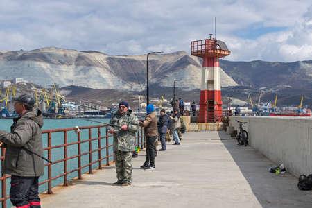 Novorossiysk, Russia - March 25: Fishermans fish near the lighthouse of the west mole in Novorossiysk on March 25, 2019 in Novorossiysk, Russia.
