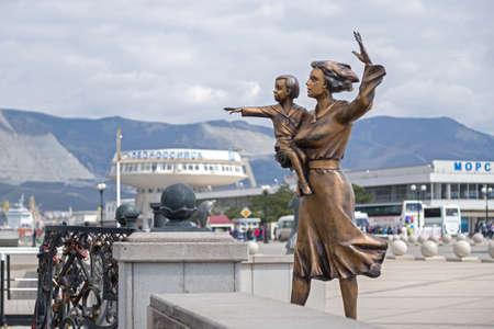 Novorossiysk, Russia - March 25: Woman with child waiting for a seaman sculpture in Novorossiysk on March 25, 2019 in Novorossiysk, Russia.