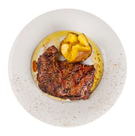 grilled potato: veal steak with grilled potato on a dish isolated