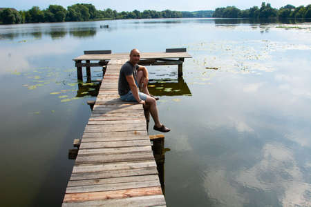 view of bald boy with casual clothing on wooden pier. summer day. Concept freedom