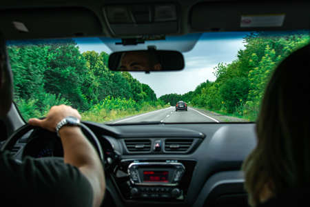 Hands of a driver on steering wheel of a car and empty asphalt road. Forest on the sides