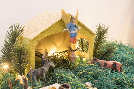 Christmas Manger and yellow lights whit yellow house and angel on top, green grass, gray donkey and brown ox, Holy Mary and Joseph toys.