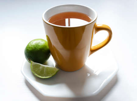 A yellow mug with Colombian traditional hot drink knowed as AGUA DE PANELA with lemon and white background. This hot drink is useful to a illness and its used to a meal too.