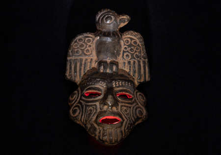 An ancient ceramic pre columbus mask based in American indigenous tribes art illuminated by red light inside and white light over black background Фото со стока