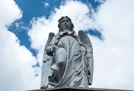 An old angel sculpture looking down in low angle shooting in top of mausoleum cemetery. Blue and cloudy sky at background