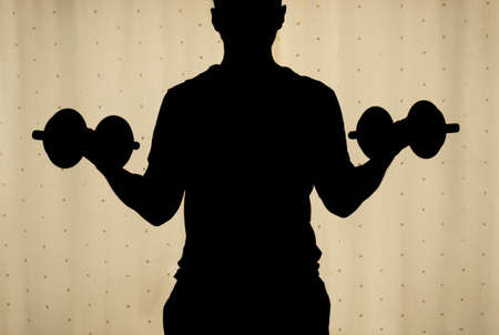 Silhouette of a back young man making a biceps dumbbell curl with yellow curtains at background. Ideal for fitness, sports, home workout, Indoor exercise and healthy life.