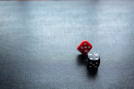 Closeup to a dices, one dice is black and one red dice is spinning over a black background. Ideal fo gamble, board games and bets
