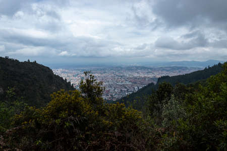 Bogota, Colombia landscape in cloudy blu sky viewed from cerros orientales or eastern hills with endemic nature of rainforest