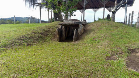An ancient mound dolmen. Monolithic tomb formed with volcanic rocks into grass at Colombian San Agustin archaeological park. antique pre columbus culture. Stock Photo
