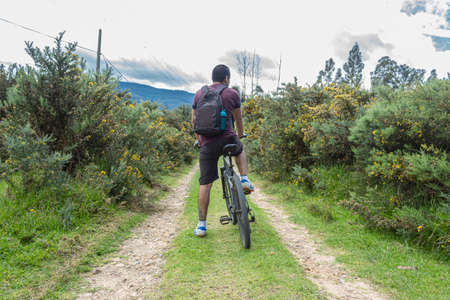 An Afrodescentand man turned his back riding a bike mountain in sand path in middle of nature. Adventure and cycling concept