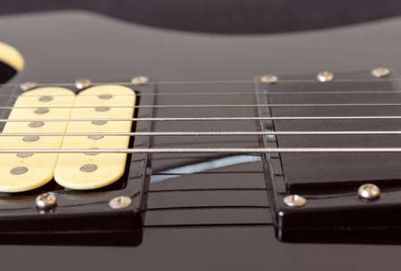 closeup to a six black electric guitar strings, wooden fretboard and microphones. Instruments and music concept Stock Photo