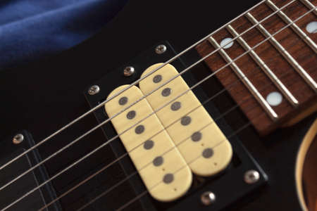 closeup to a six electric guitar strings, wooden fretboard and microphones. Instruments and music concept