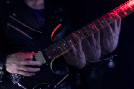 Long Exposure picture of a man wearing a leather jacket playing a black and yellow electric guitar at indoor illuminated with red and white lights. Rock and music concept