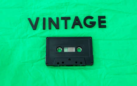 Top View of VINTAGE black lettering word with an old black cassette over a green cloth. Fashion and music concept