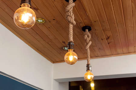 three artesanal yellow light bulbes with wooden roof and blue & white paiting. Interior design concept