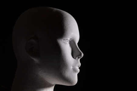 Closep to a white female manikin head portrait with black background. Photography, arts and anatomy concept