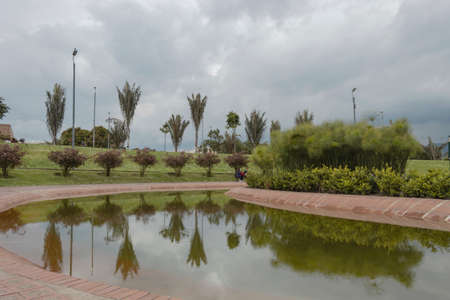 A beautiful bogota metropolitan park scene with water tree reflection and gray cloudy sky at background Banque d'images
