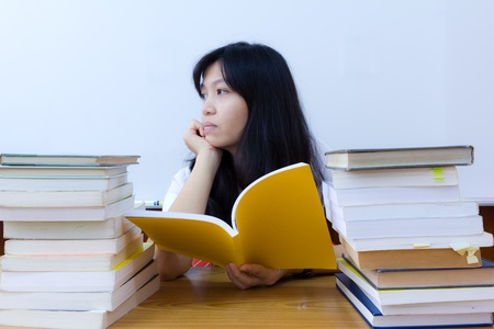 wearied: Bored college student in uniform with stack of books