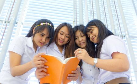 wearied: Group of College students in uniform reading together  Stock Photo