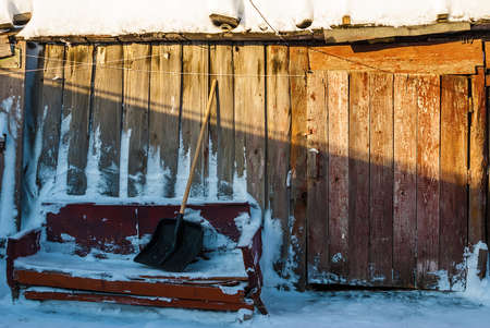 old barn in winter: The facade of the old rustic barn in winter sunny day