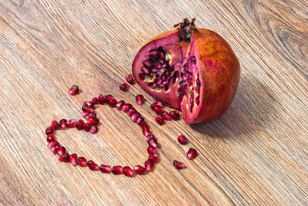 holiday food: Pomegranate and its seeds laid out in the shape of heart on a wooden texture Stock Photo