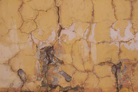 crumbling: The texture of a wall with cracks and crumbling yellow plaster