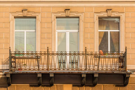 architectonics: Two windows and door in a row and balcony on facade of urban apartment building front view, St. Petersburg, Russia