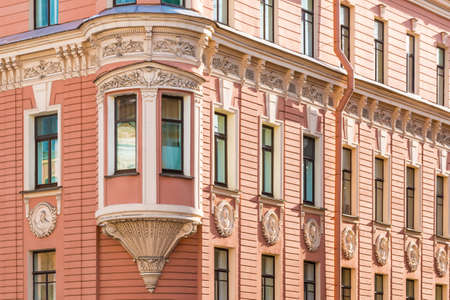 many windows: Many windows in row and bay window on corner of facade of urban apartment building angle view, St. Petersburg, Russia