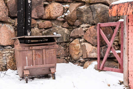 wicket: Garbage container and wicket near a stone wall in winter scene Stock Photo