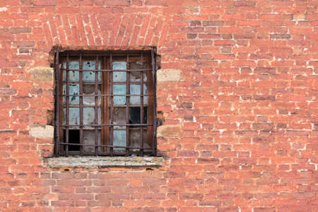 lattice window: Broken window with lattice on the brick facade of an abandoned building