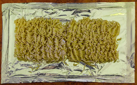 instant noodle: Dry instant noodle on foil lying on the table closeup