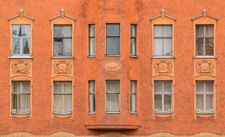 bow window: Several windows in a row and bay window on facade of urban apartment building front view, St. Petersburg, Russia
