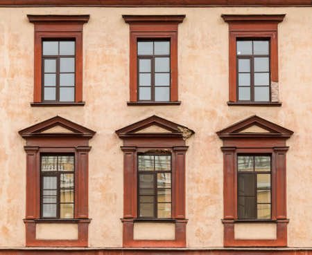 ledge: Several windows in a row on facade of urban apartment building front view, St. Petersburg, Russia