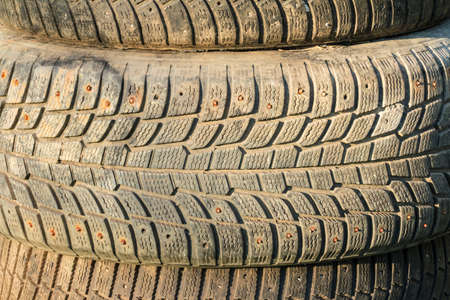 treads: A stack of old tires with textured tread on sunlight closeup