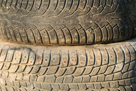 A stack of old tires with textured tread on sunlight closeup