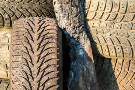 charred: A stack of old tires with textured tread and charred plank on sunlight closeup