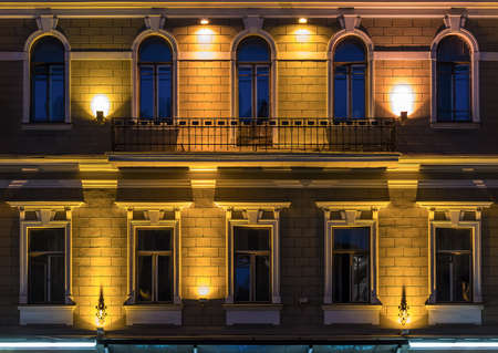 illuminating: Several windows in a row and balcony on night illuminated facade of urban office building front view, St. Petersburg, Russia
