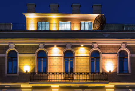 mansard: Several windows in a row and balcony on night illuminated facade and mansard of urban office building front view, St. Petersburg, Russia