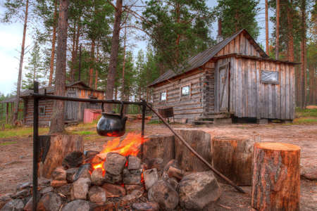 Kettle over the campfire on a background of the hut and a banya in the forest Stock Photo