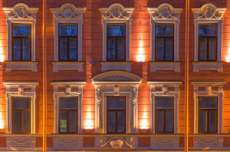 Several windows in a row on night illuminated facade of urban office building front view, St. Petersburg, Russia 스톡 콘텐츠