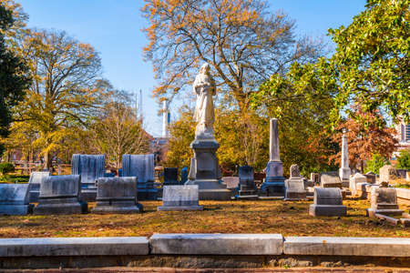 Group of tombstones and sculpture of Virgin Mary on the Oakland Cemetery in sunny autumn day, Atlanta, USA