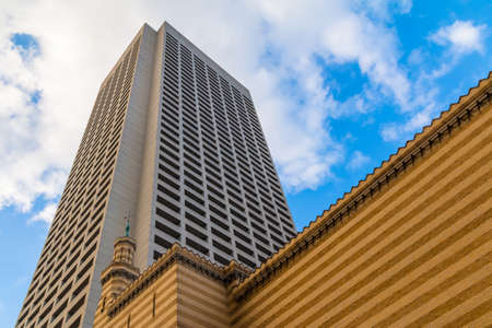 Bottom view of the skyscraper rising above the brick facade on the background of cloudy sky, Atlanta, USA Stock Photo