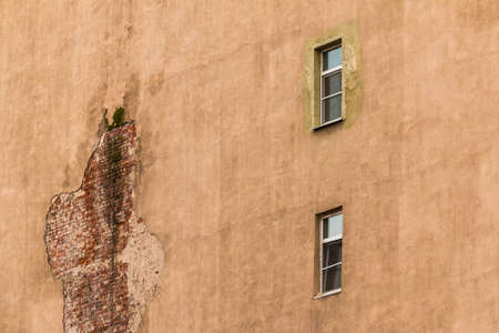 scabrous: Two windows in a row on facade of urban apartment building, St. Petersburg, Russia