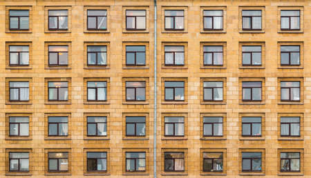 Many windows in a row on facade of urban apartment building front view, St. Petersburg, Russia