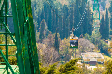 The cableway and the cabin over the city on the background of Arboretum in sunny day, Sochi, Russia Stock Photo