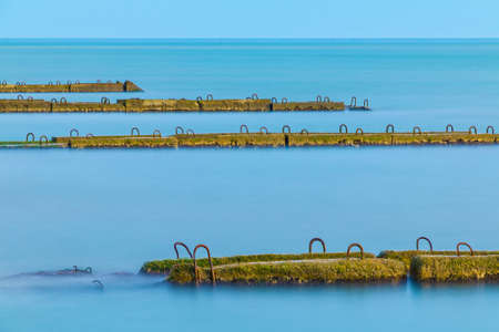 Long exposure view of row of the concrete moles in the sea and horizon far away in sunny day Stock Photo